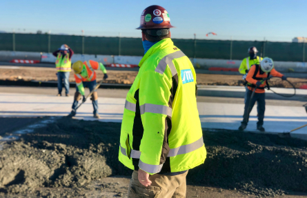 airport with workers laying cement